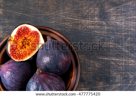Ripe raw figs on a black wooden table, top view, copy space