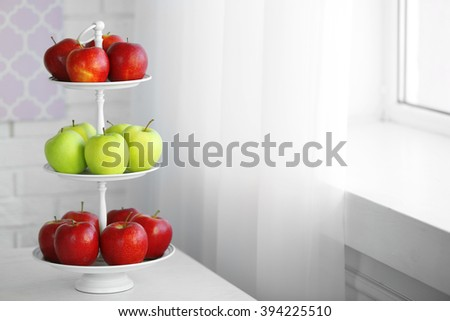 Ripe red and green apples on a stand in kitchen - stock photo
