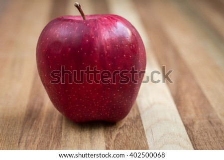Ripe red apple on wooden background - stock photo