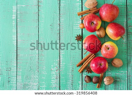Ripe red apples and spices on a bright wooden background. Top view - stock photo