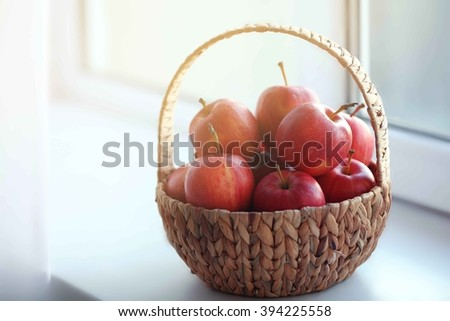Ripe red apples in basket on windowsill - stock photo