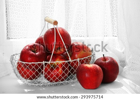 Ripe red apples in metal basket on windowsill - stock photo