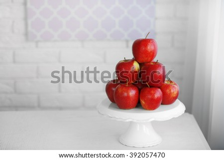 Ripe red apples on a stand in kitchen - stock photo