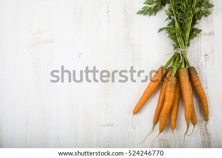 Ripe red carrots with leaves on a wooden table close-up. Fresh vegetables. Healthy eating.