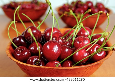 Ripe red cherries in a wooden bowls on wooden table, fruit, spring