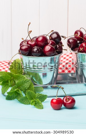 Ripe red cherries in blue wooden table background. - stock photo
