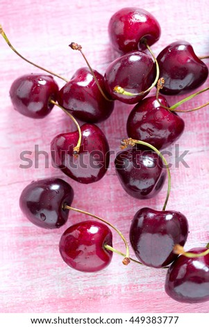 ripe red cherries on wooden surface