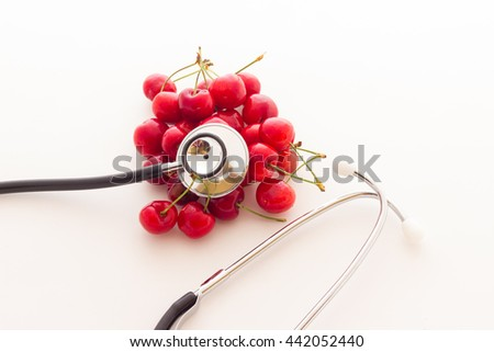 Ripe red cherry berries with  stethoscope - stock photo