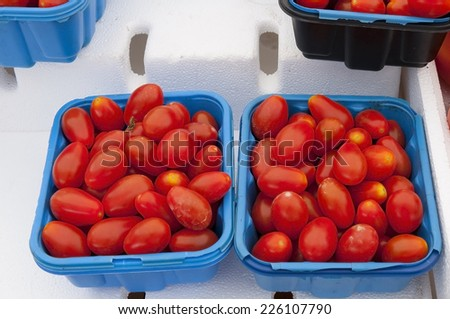 Ripe red Cherry Tomatoes at a farmers market ready to sell - stock photo