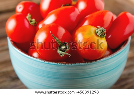 Ripe red cherry tomatoes on blue plate. Dark wood background. - stock photo
