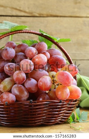 ripe red organic grapes in a basket on a wooden table