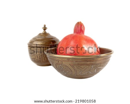 Ripe red Pomegranate in the ancient carved vase isolated over  white  background  in vintage style - stock photo