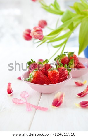 Ripe red strawberries and pink tulips