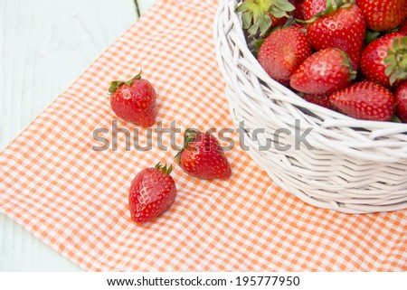 Ripe red strawberries in a white basket on wooden surface lies