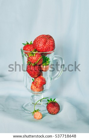 Ripe red strawberries in transparent glass high glass on blue background