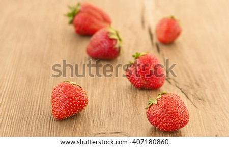 Ripe red strawberries on a wooden background. Strawberries over wooden table background with copy space. - stock photo