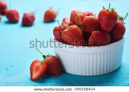 Ripe red strawberries on blue wooden table. - stock photo
