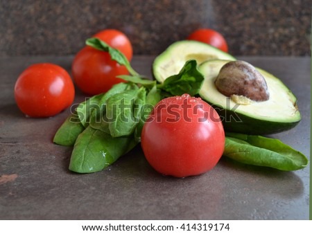 Ripe red tomato with drops of the water, avocado halves, spinach are on the stone kitchen background. Favorite healthy snack. Healthy dinner inspirations for every day. Magical combination. - stock photo
