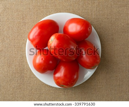 Ripe Roma Tomatoes on a white plate with natural light on a burlap tablecloth. - stock photo
