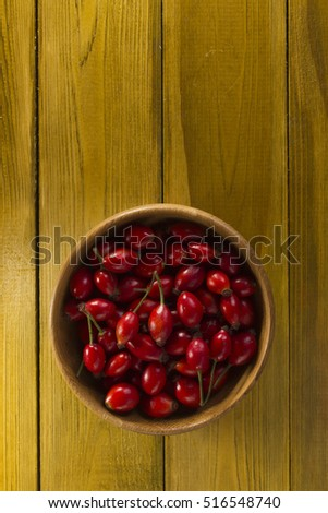 Ripe rosehips in wooden plate on a wooden background