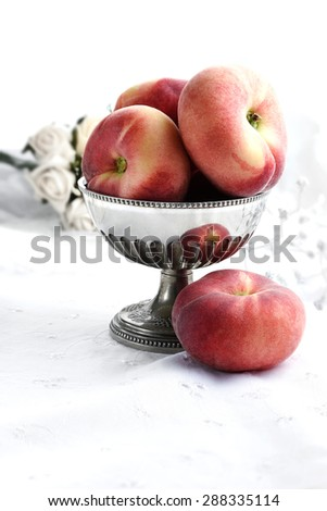 Ripe saturn peaches, also known as flat or donut peaches in an antique silver bowl in a Victorian setting against a white background. Generous copy space available. - stock photo