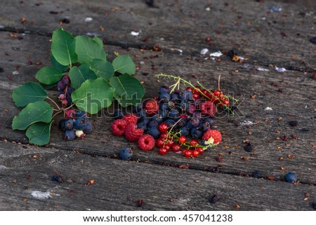 Ripe shadberry, redcurrant, raspberry with branch and leaves scattered on the weathered wooden table in garden - stock photo