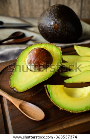 Ripe slice avocado on wooden cutting board on wooden table - stock photo