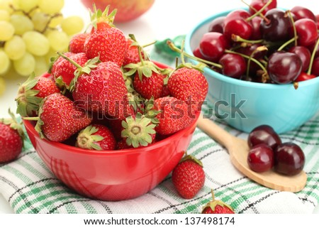 Ripe strawberries and cherry berries in bowls, grapes and apple close up - stock photo