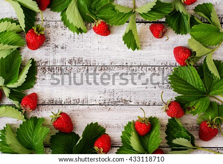 Ripe strawberries and leaves on a light wooden background. Top view - stock photo