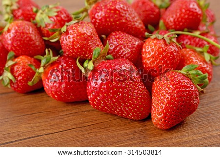 Ripe strawberries heart shaped on wooden table, closeup - stock photo
