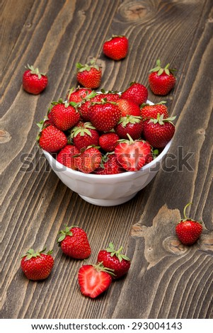 Ripe strawberries in a white bowl on a wooden table