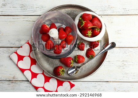 Ripe strawberries in blender on metal tray on wooden table, top view - stock photo