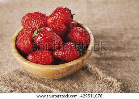 ripe strawberries in bowl on burlap.   - stock photo