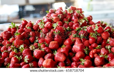 ripe strawberries in the market. Summer fruits and berries. The strawberry is folded into a big hill