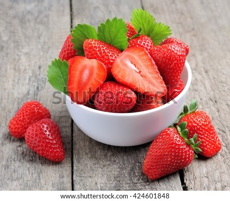 Ripe strawberries on the old wooden textured table - stock photo