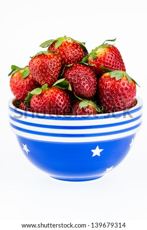 Ripe strawberries piled high in a blue and white bowl isolated against a white background. - stock photo