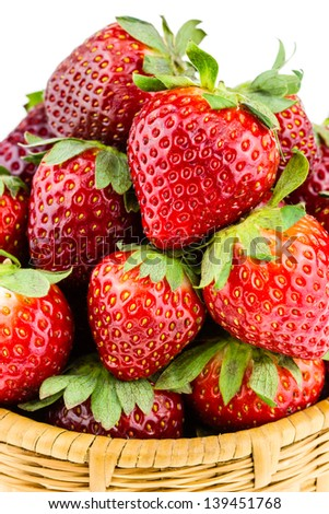 Ripe strawberries piled high in a wicker basket isolated against a white background. - stock photo