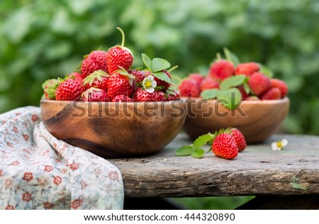 Ripe strawberries with leaves in a bowl on wooden table on blurred background. Tasty and healthy berries. - stock photo