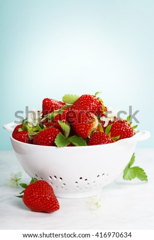 Ripe strawberries with leaves in white colander on marble table with blue background - stock photo