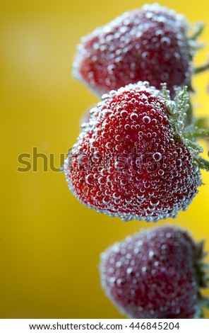 Ripe strawberries with water bubbles on yellow background. Selective focus. - stock photo