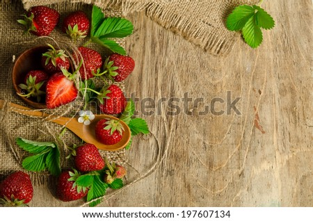 Ripe Strawberry in a wooden Bowl on burlap background - stock photo