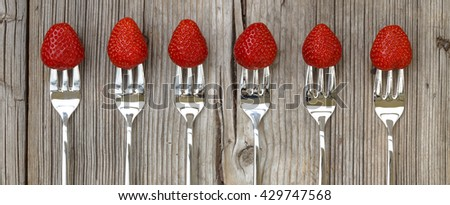 Ripe strawberry on a fork on a worn wooden background. - stock photo