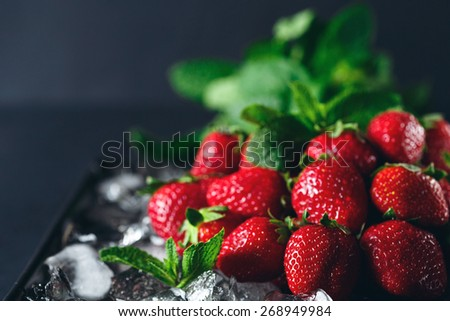 Ripe strawberry on ice with mint leaf. Dark background. Selective focus. - stock photo