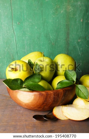 Ripe sweet apples with leaves in bowl on wooden background - stock photo