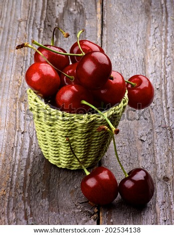 Ripe Sweet Cherries in Green Wicker Basket isolated on Rustic Wooden background - stock photo