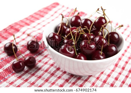 Ripe sweet cherry in a bowl on a checkered napkin
