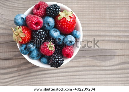 Ripe sweet different berries in bowl. Close up, top view, high resolution product. Harvest Concept - stock photo