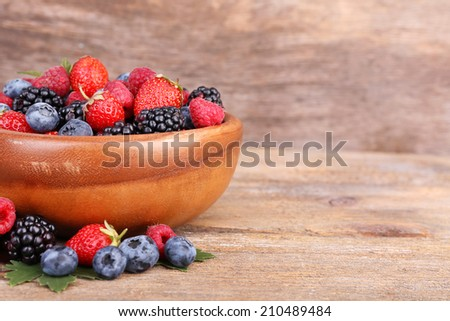 Ripe sweet different berries in bowl, on old wooden table - stock photo
