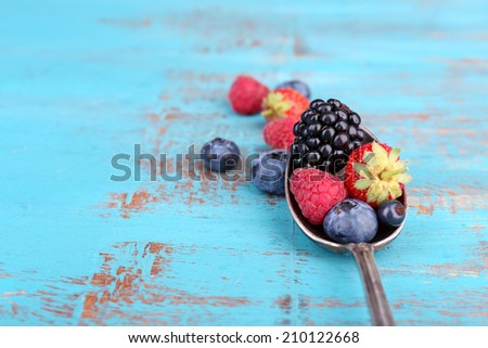 Ripe sweet different berries in vintage spoon, on old wooden table - stock photo