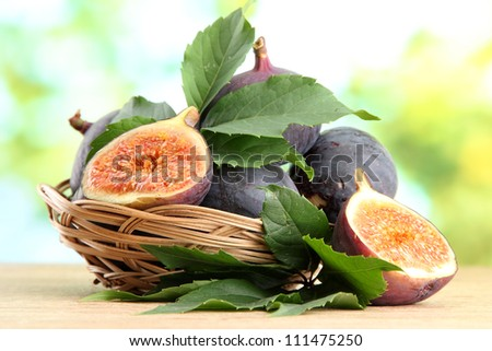 Ripe sweet figs with leaves in basket, on wooden table, on green background - stock photo